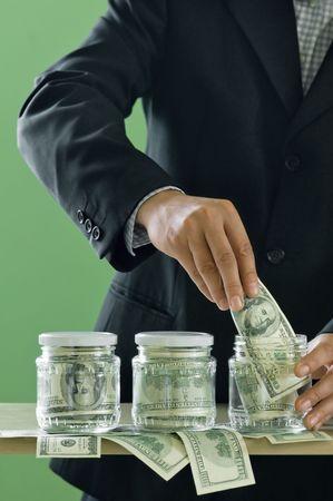 businessman put dollars in glass jar photo