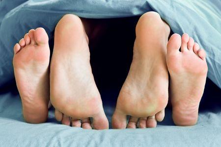 sexo cama: Pareja pie en la cama primer plano