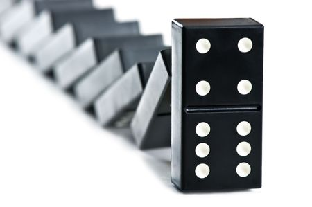 cause and effect: falling domino brick close up