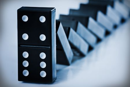 cause and effect: falling domino concept close up Stock Photo