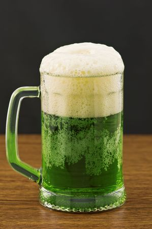 Mug of green beer on wooden counter photo