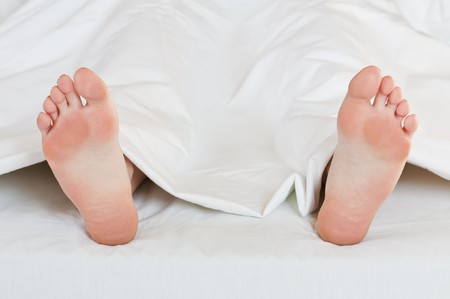 girl foots in bed closeup photo