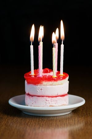 cake with candle on wood table photo