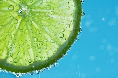 lime with bubbles on blue background photo