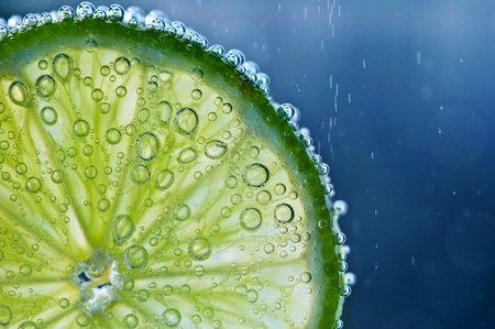 lime with bubbles on blue background Stock Photo