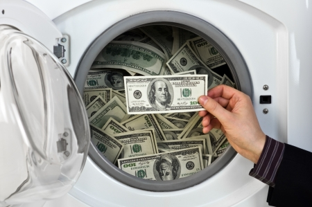 money laundering: money in washing machine close up