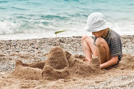 Junge, der Sandburg am Strand