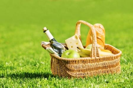 corbeille de fruits: panier pique-nique sur la pelouse verte