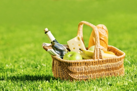 apples basket: picnic basket on green lawn Stock Photo