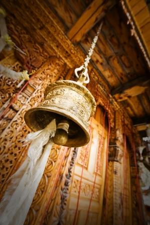 gold tibetan bell near old temple