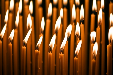 church group: burning orange candles close up Stock Photo