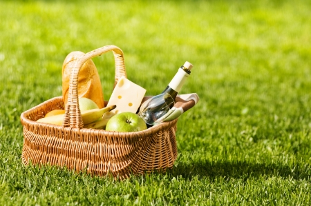 bread basket: picnic basket on green lawn Stock Photo