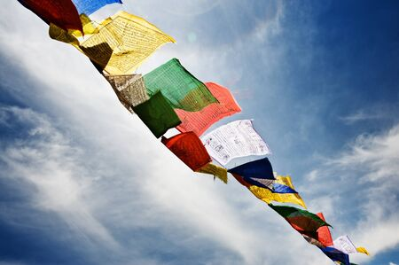 tibetan flags with mantra on sky background photo