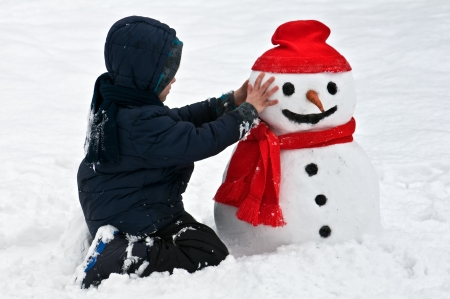 boy with snowman on winter park photo
