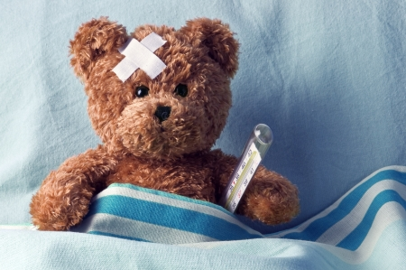 sick teddy bear: bear in bed with thermometer and plaster
