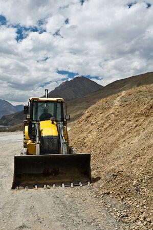 front loader: excavadora amarilla en carretera de montaña Foto de archivo
