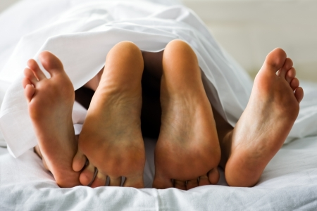 two pair legs in bed