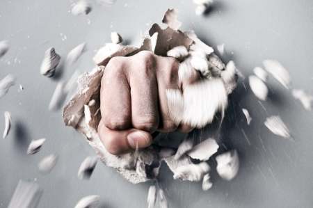 una pared se rompe a través de un puño