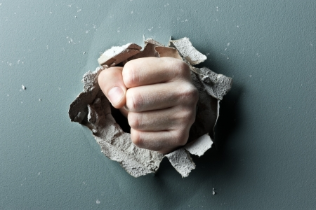 demolishing: a wall is broken through by a fist