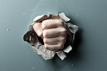 pu�os cerrados: una pared se rompe a trav�s de un pu�o