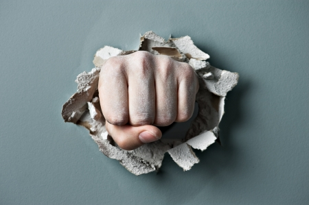 hole in wall: a wall is broken through by a fist