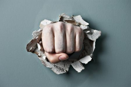 pared rota: una pared se rompe a través de un puño
