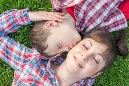boy kissing his mom on grass photo