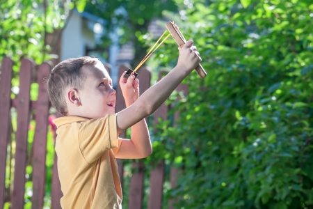 elastic: young boy with slingshot shooting