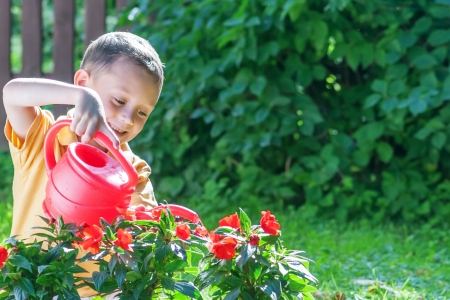 boy with watering can on garden photo