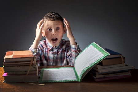 difficult task: boy does a home task Stock Photo
