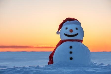 オレンジ色の夕日に雪だるま 写真素材