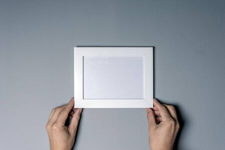 picture frame on wall: empty photo frame in woman hands