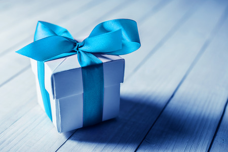 blue ribbon: single gift box on wood table