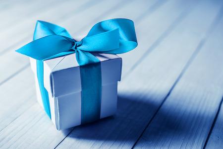 blue ribbon: single gift box on wood table
