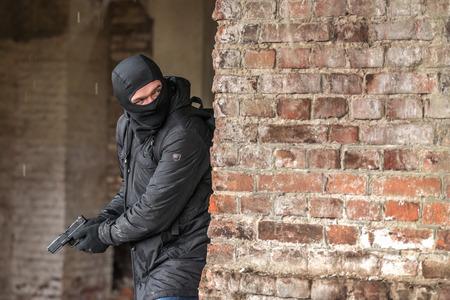 hombre disparando: hombre en la máscara con pistola Foto de archivo
