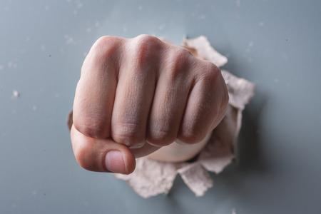 broken through: a wall is broken through by a fist