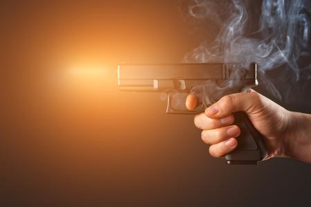 gun shot: shot from a handgun with fire and smoke Stock Photo
