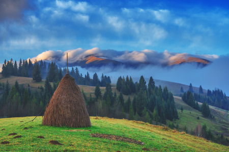 alone haystack in foggy mountain