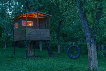Haus auf Baum im Abendgarten Standard-Bild - 36965976
