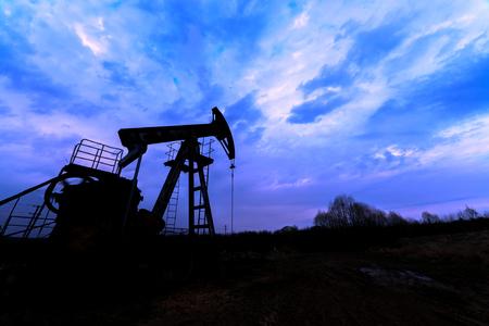oilwell: oil pump silhouette against blue sky