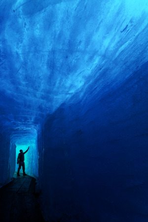 rhone: Man silhouette in ice cave, Rhone glacier, Switzerland Stock Photo