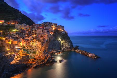 Niesamowity widok na Manarola miasta wieczorem światła z przybrzeżnych skał na pierwszym planie. Park Narodowy Cinque Terre, Liguria, Włochy, Europa.