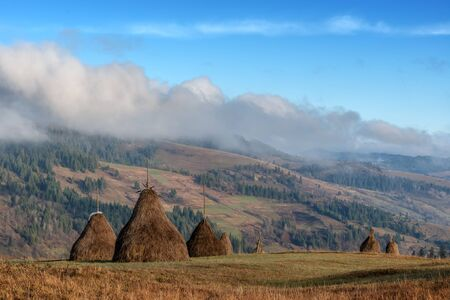 rural scene: Amazing rural scene on autumn valley. Wooden fence and haystack on a foreground. Carpathians, Ukraine, Europe. Stock Photo