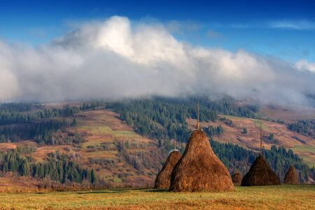 wooden fence: Amazing rural scene on autumn valley. Wooden fence and haystack on a foreground. Carpathians, Ukraine, Europe. Stock Photo