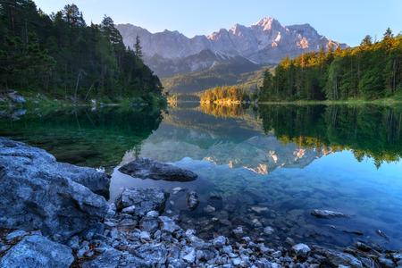 water  scenic: Fantastic sundown on mountain lake Eibsee, located in the Bavaria, Germany. Dramatic unusual scene. Alps, Europe. Stock Photo