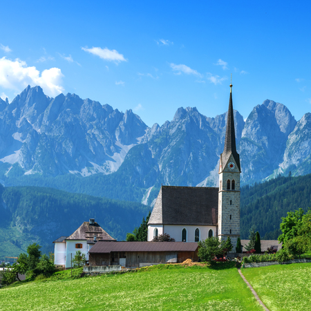 cristianismo: churh el cristianismo en el pueblo de Gosau en el día soleado. Alpes, Austria, Europa. Foto de archivo