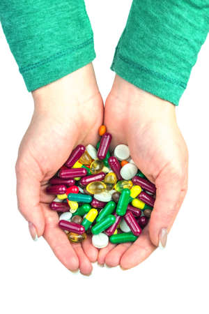 medicate: many color pills in hand isolated Stock Photo