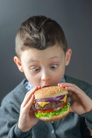 niños comiendo: cheeseburger en niño de la mano de cerca
