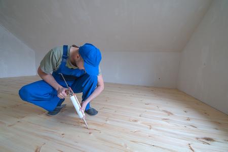 silicio: Suelo de madera barnizada. Trabajador con el arma de silicio. Foto de archivo