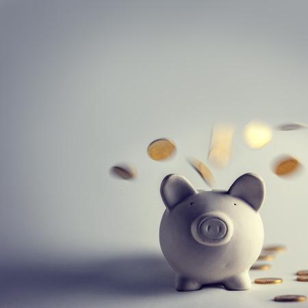 economia: caja de dinero de cerdo con monedas de oro